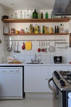 Com a bancada revestida em azulejos brancos iguais aos da parede, o espaço dá a sensação de ser mais amplo do que realmente é. Os utensílios pendurados são ao mesmo tempo práticos e decorativos Home Decor Shelves, Home Decor Kitchen, Diy Kitchen, Kitchen Cabinets, Small Kitchen Solutions, Small Space Kitchen, Kitchen Modular, Indian Home Decor, Diy Home Decor Projects