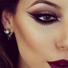 A bold eye look with exaggerated liner, contour and lipstick