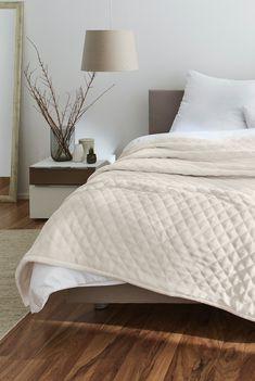 Beige quilt, bedroom in neutral hues.