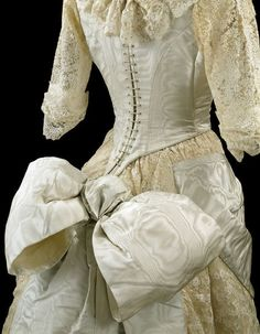 Floor-length ball gown consisting of a bodice and skirt in moiré silk overlaid and trimmed with machine lace. c. 1885.