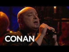 "David Draiman, lead singer of the band Disturbed, sings the Simon and Garfunkel classic ""The Sound Of Silence"" on the Conan O'Brien show. Give a listen. Rock Music, Live Music, My Music, Simon Garfunkel, Heavy Metal Bands, Sound Of Silence Disturbed, Paul Simon, Soundtrack, David Draiman"