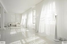 Sheer white cutains over white plantation shutters in larger room create beautiful shadows and movement