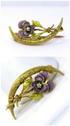 An antique honeymoon brooch in gold with enamel details and a diamond-centered pansy.