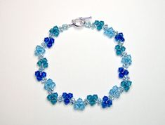 A delicate bracelet using swarovski bicones in different shades of blue. The colours used are capri blue, aquamarine and indicolite, also used are light aqua AB seed beads and finished with a silver plated toggle clasp. Length of bracelet including clasp is 19 cm (7.5 inches) which