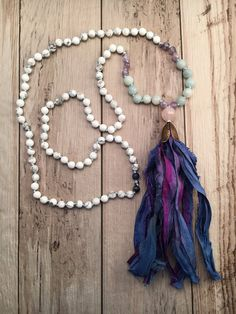 This gorgeous mala necklace has the most peaceful, calming colors. Howlite, Amazonite, and Amethyst are hand-knotted on sky blue cord and finished with a hand-made sari silk tassel. Two Sodalite Beads meet at the top. Beautiful faceted large Rose Quartz Guru bead sits atop the tassel. The