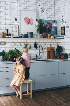 gorgeous Swedish kitchen inspiration with white tile backsplash and the little girls playing in sweet babydoll dresses