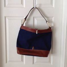 """Authentic Le Tanneur leather and canvas purse Authentic Le Tanneur navy canvas and leather hobo purse. Used once. Clip closure at front. Leather handle. One small interior pocket. hobo marine design. 13"""" in height and 17""""in width Le Tanneur Bags Hobos"""