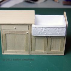 Dollhouse scale butler's sink set in a cabinet base ready for the countertop.