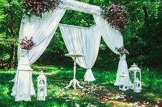 Wedding arch with white fabrics and flowers and small table in the forest. Candles and flower petals on the ground. Green grass and trees. Flower Petals, Flowers, Small Tables, Green Grass, White Fabrics, Garden Sculpture, Wedding Decorations, Candles, Outdoor Decor