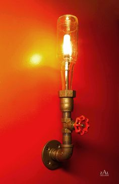 Wall lamp made from beer bottle & plumbing pipe.