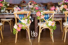 floral detailing on bride and groom chair by Blush Botanicals.  Coral peonies and garden foliage photo by The Youngrens