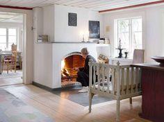 1800-TAℒSℋUS ℳᏋᎠ ᏰᏋVAℛAᎠ ᏣℋAℛℳ: Takhöjden i den tillbyggda hallandslängan från mitten av 1800-talet är låg men rummen känns rymliga och ljusa, mycket tack vare att det finns fönster åt båda sidor. Det finns heller inga gardiner i vägen. Anneli tänder gärna en värmande brasa under kyliga dagar. Från den vackra soffan kan hon sedan njuta av eldens dans i den stora öppna spisen.