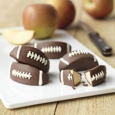 Candy-Coated Apple Football Treats - Dipped apple wedges decorated like footballs make a sweet treat for your favorite playoff celebration, tailgate party or after-game snack for the tiniest tackle on the team. Use Wilton Short Dipping Containers to easily dip apple wedges in delicious Candy Melts candy.