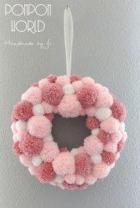 Corona navideña rosada hecha con pompones de lana