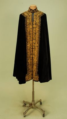 Front View GOLD METALLIC EMBROIDERED VELVET CAPE, c. 1900. Black having stand-up collar with two hook & eye closures, decorated on collar, around neck and front edges with heavy gold floral embroidery and gold sequins, lined in blue satin. Length 40.