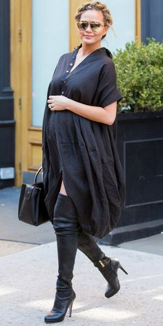 Chrissy Teigen in a flowy midi dress with a thigh-high slit, perfectly showing off her over-the-knee boots.
