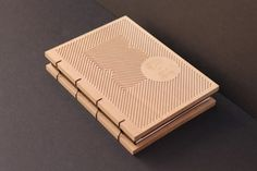 A book with an egraved, wooden cover and exposed binding.