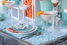mesa posta com jogo americano estampado em azul, pratos brancos, prato de sobremesa azul em vidro, prato floral, taças brancas e arranjos de flores coral.