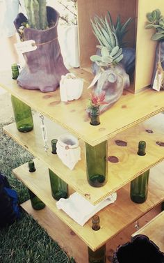 table made from wine bottles and wood with holes drilled.