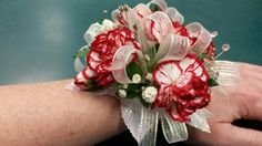 White with red edge mini carnations with baby's breath with white leaves and white ribbon wrist corsage