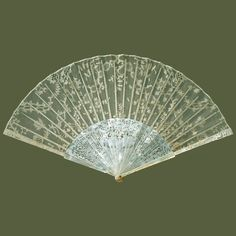 Brussels lace fan c. 1780. Cream silk needle-lace leaf; carved, pierced and incised mother-of-pearl guards (matching) and sticks, painted bamboo ribs