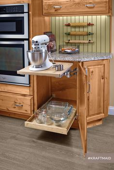 Save your back by storing a heavy mixer on a shelf that swings up from below the countertop and then locks in place at counter level. (KraftMaid cabinets in Natural Rustic Alder)