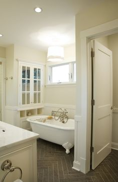 source: Scott Lyon & Company      Stunning bathroom with water closet, board and batten walls, dark gray herringbone slate tile floor and elegant claw foot tub. White wainscotting and vanity with nickel fixtures. Light beige walls and contemporary scalloped drum pendant over bath.