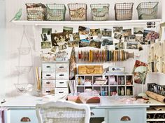 This home work space was appointed with cubbies, drawers, vintage cookie tins, baskets, and wire racks to keep items handy and add personality. A bath towel bar was installed to hold spools of ribbon, and a curtain rod with curtain clips provides space to hang photos, postcards, or inspirational ephemera.