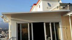 Pergola de aluminio con techo de chapa con cerramiento de c.m. de aluminio