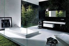 Melt into the floor with this sunken soaking tub. A patch of lawn just outside floor-to-ceiling glass walls helps to keep a stressful day in perspective. #bathroom #interiordesign #decor