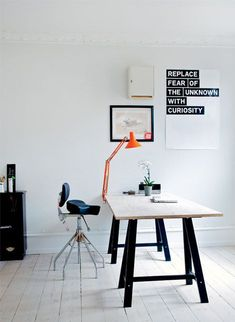 Adjustable, industrial style stool, black and white workspace and orange lamp
