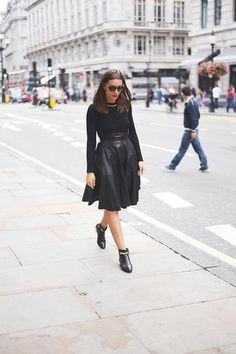 All-Black Outfits for Fall: Black leather midi skirt, black booties, and a long sleeve knit shirt.