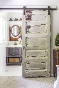 Instantly countrify your master bedroom by hanging a shabby chic door at the en suite entryway. Learn more at Shades of Blue Interiors.