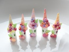 A tiny little fairy village of 5 mini fairy flower houses handmade from polymer clay and decorated with acrylic paint in pastel colours. The houses