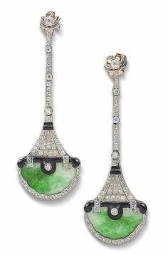 A pair of enamel, jade and diamond pendent earrings.  Each designed as a highly stylised pagoda, with carved jade base and black enamel overhanging storey, supporting an articulated tapering tower surmount pierced and millegrain-set throughout with old brilliant and rose-cut diamonds and black enamel detail, later post fittings, cased
