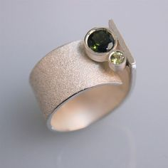 Andreas Schiffler | This ring is made of sterling silver. It has a 3mm periodot and a 6mm turmaline. Love it.