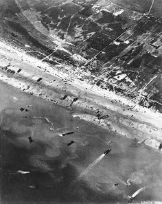 D-Day: The Normandy Invasion. Army Air Corps photographers documented D-Day beach traffic, as photographed from a Ninth Air Force bomber on June 6, 1944. Note vehicle lanes leading away from the landing areas, and landing craft left aground by the tide. Some of the black dots are dead soldiers