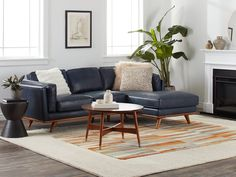 A simple setup of a mid-century living room: the leather couch with wooden legs, perfectly matching the wooden coffee table, completed by the dark side table and the light, mid-century rug. The plants and vases top it off with more mid-century style.