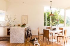 """""""Our kitchen is by far the center of the household. The Cararra marble waterfall counter serves as a place of social gathering a workspace and of course the most popular spot for our family to enjoy a meal."""" - by onekingslane Dining Area, Kitchen Dining, Dining Table, Dining Rooms, Kitchen Tips, Kitchen Ideas, Best Office, Minimalist Room, Love Home"""