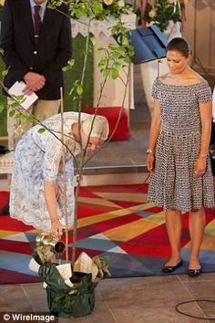 Princess Mette-Marit also waters the plant...