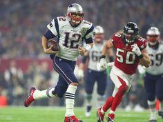 Patriots quarterback Tom Brady (12) pulls it down and