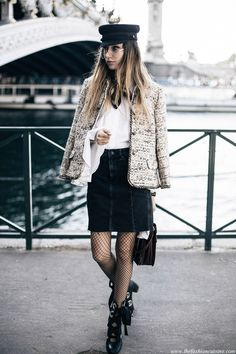 Fashion Blogger Beatrice Gutu during Paris Fashion Week wearing chanel tweed jacket with sailor cap and mini denim skirt with fishnet tights parisian style