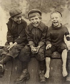 Three Happy Boys from early 1900's. Nothing more classic than three over joyous boys sitting on a fence with a ball in hand.