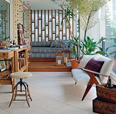 A varanda projetada pela arquiteta Gabriela Marques tem design, conforto e história. Há um sofá dos anos 1950 de José Zanine Caldas e, em um canto com velas, futons para relaxar. Para completar, a bancada de marceneiro, ofício do avô do morador