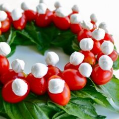 Caprese salad Christmas wreath. 1 - lay basil in circle. 2 - skewer your tomatoes & mini bocconcini with toothpicks. #HappyHolidays