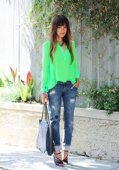 25 Stylish Outfits With Cuffed Jeans: Woman wearing cuffed boyfriend jeans together with a bright green shirt and black strappy sandals