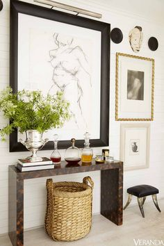 andrew brown - parsons style tortoise console + braided seagrass basket, vignette, gallery wall with interesting frames