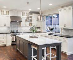 Aménagement d'un îlot central avec son plan de travail en marbre blanc dans une cuisine rayonnante et moderne avec son mobilier blanc crème élégant
