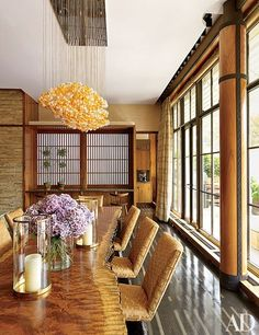 A De la Torre light fixture, comprised of orange-hued glass spheres, is suspended above a bubinga-slab dining table in a Japanese-inspired Manhattan penthouse.