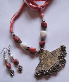 It is made of marble beads,glass,metal spacer beads with adjustable dori.It has two matching earrings.